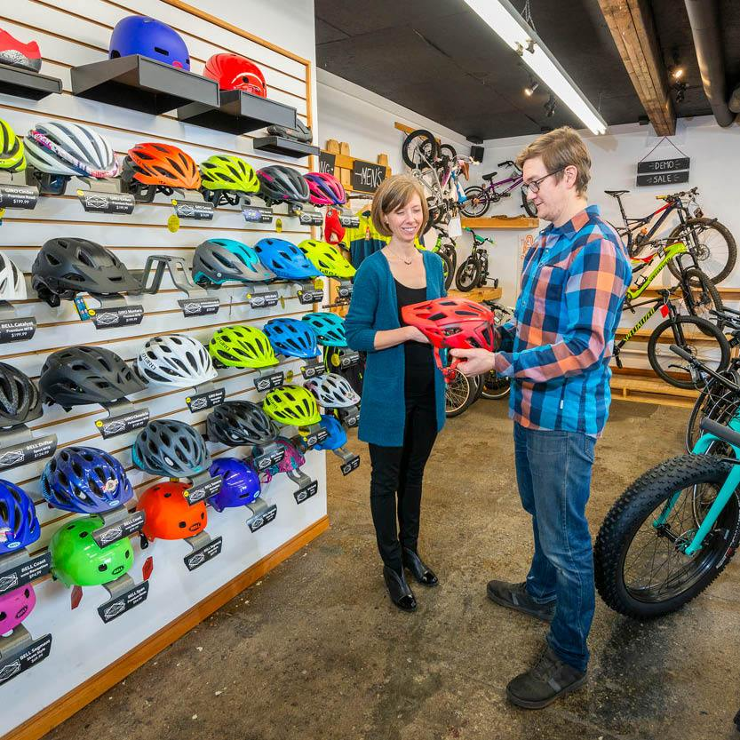 Man discussing bike helmets with woman in bike shop
