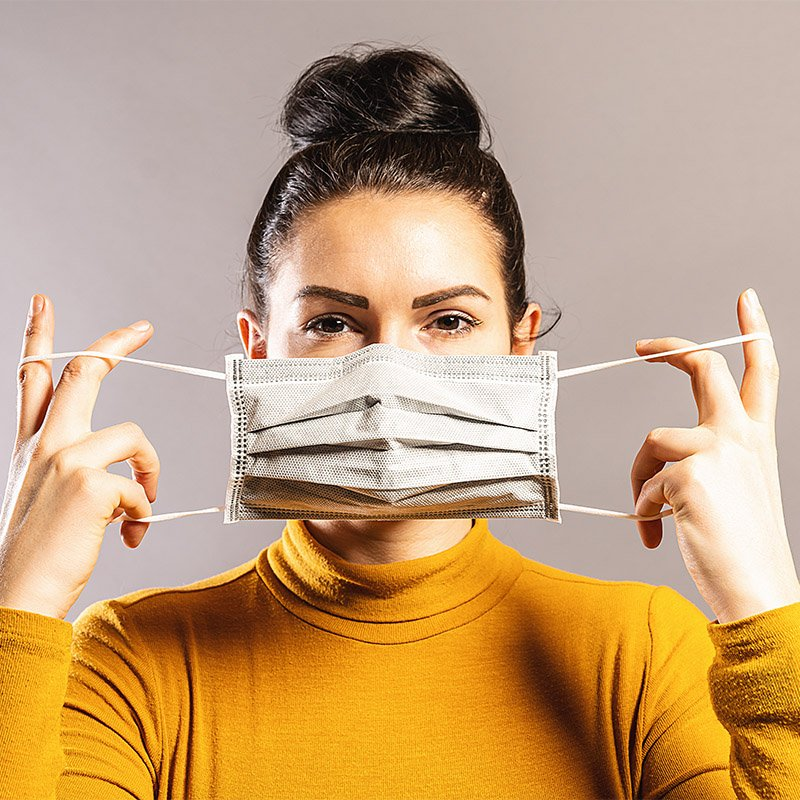 woman putting on a mask