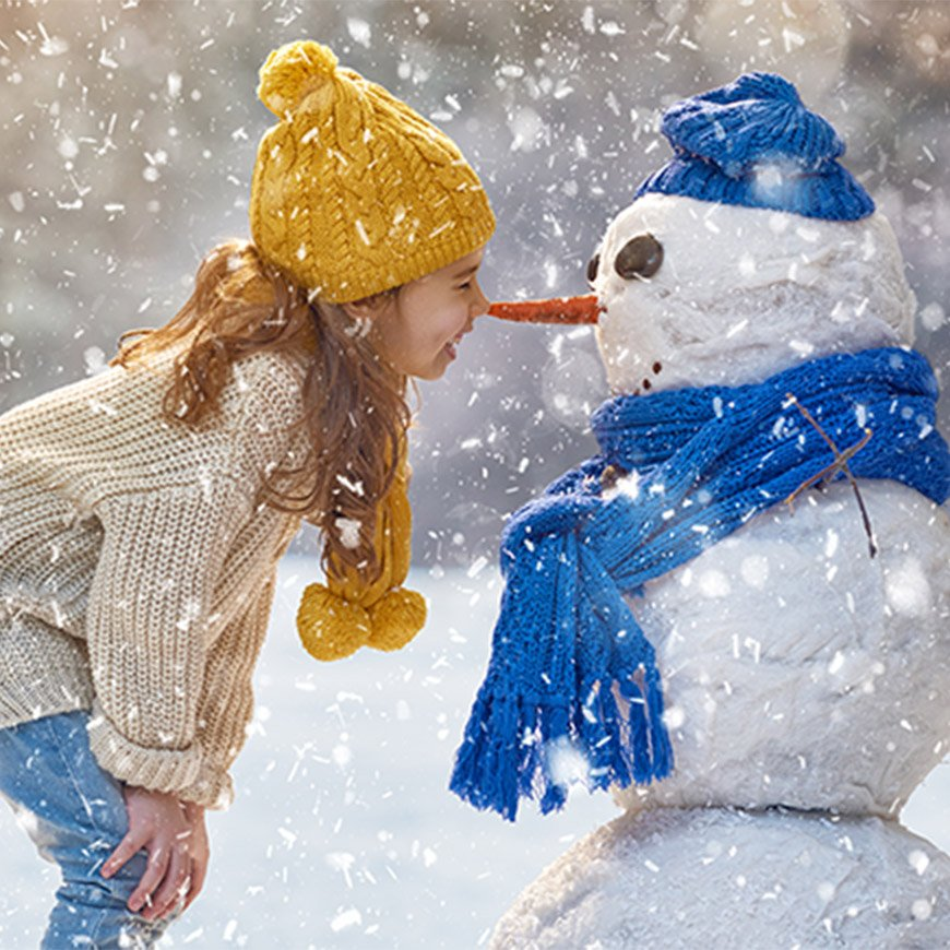 girl nose to nose with snowman