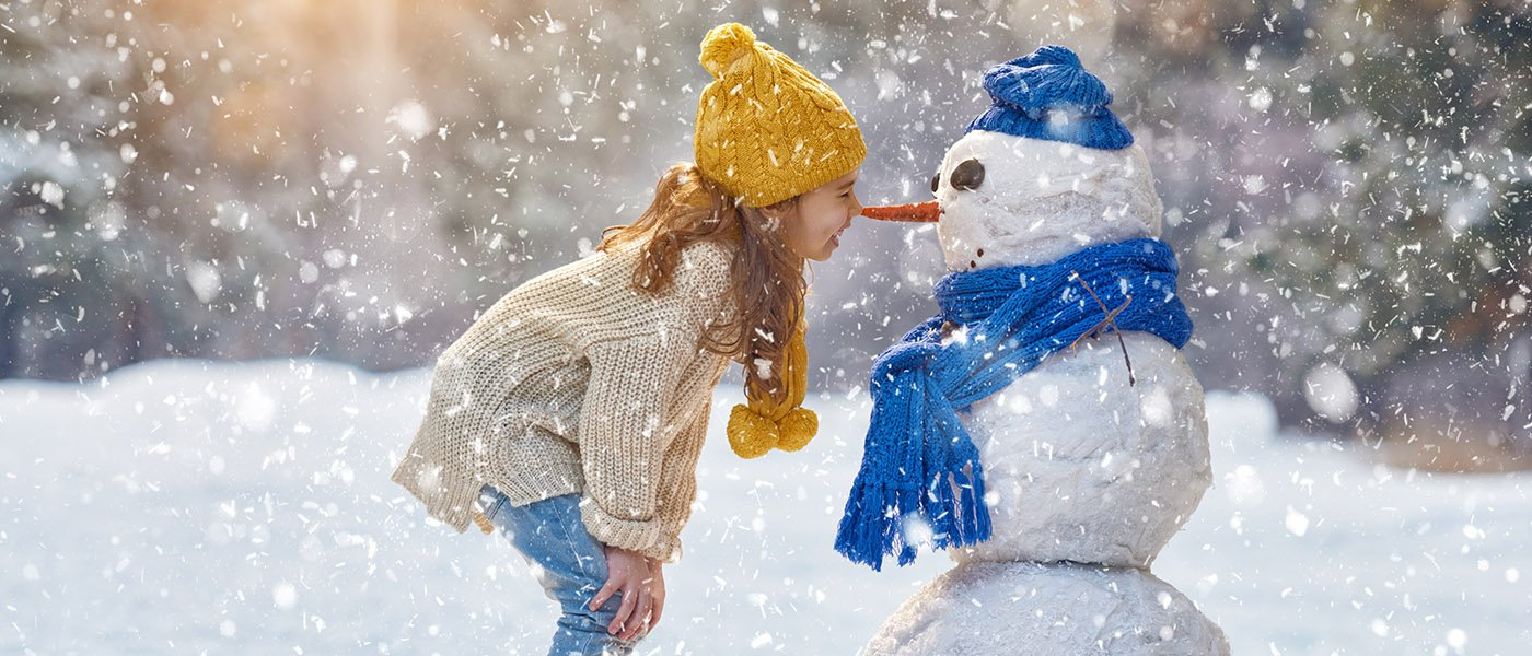 little girl nose to nose with a snowman