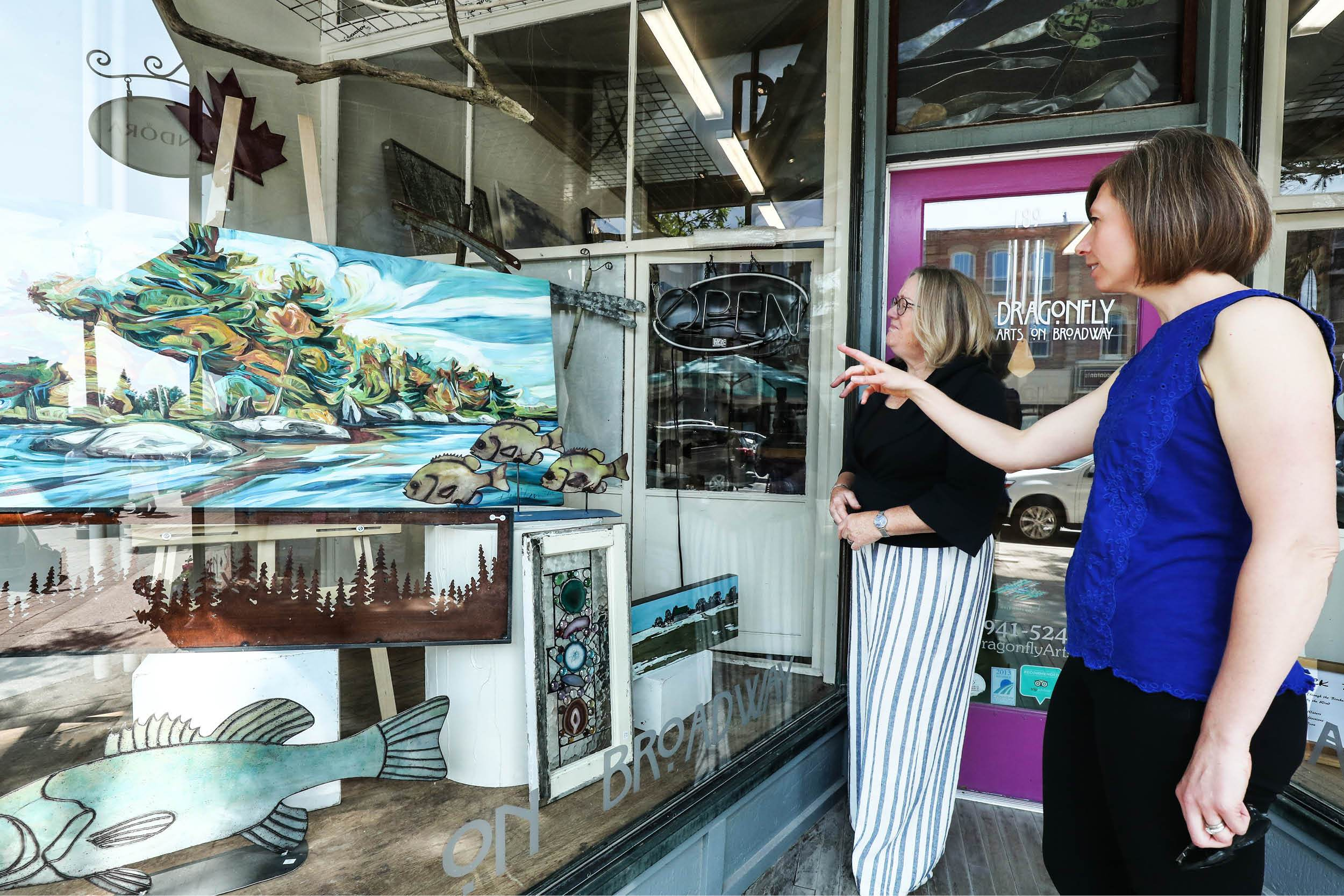 Two women viewing artwork in a shop window