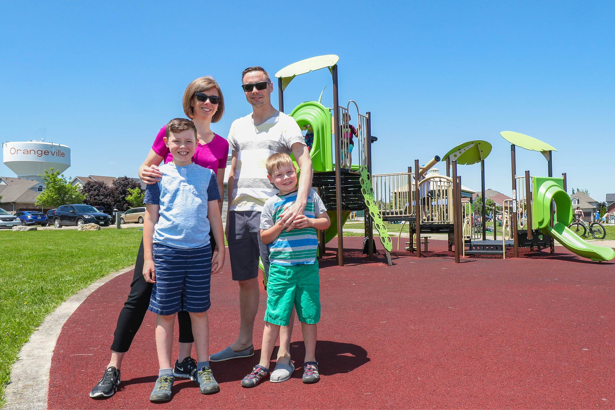 Family of four standing in playground
