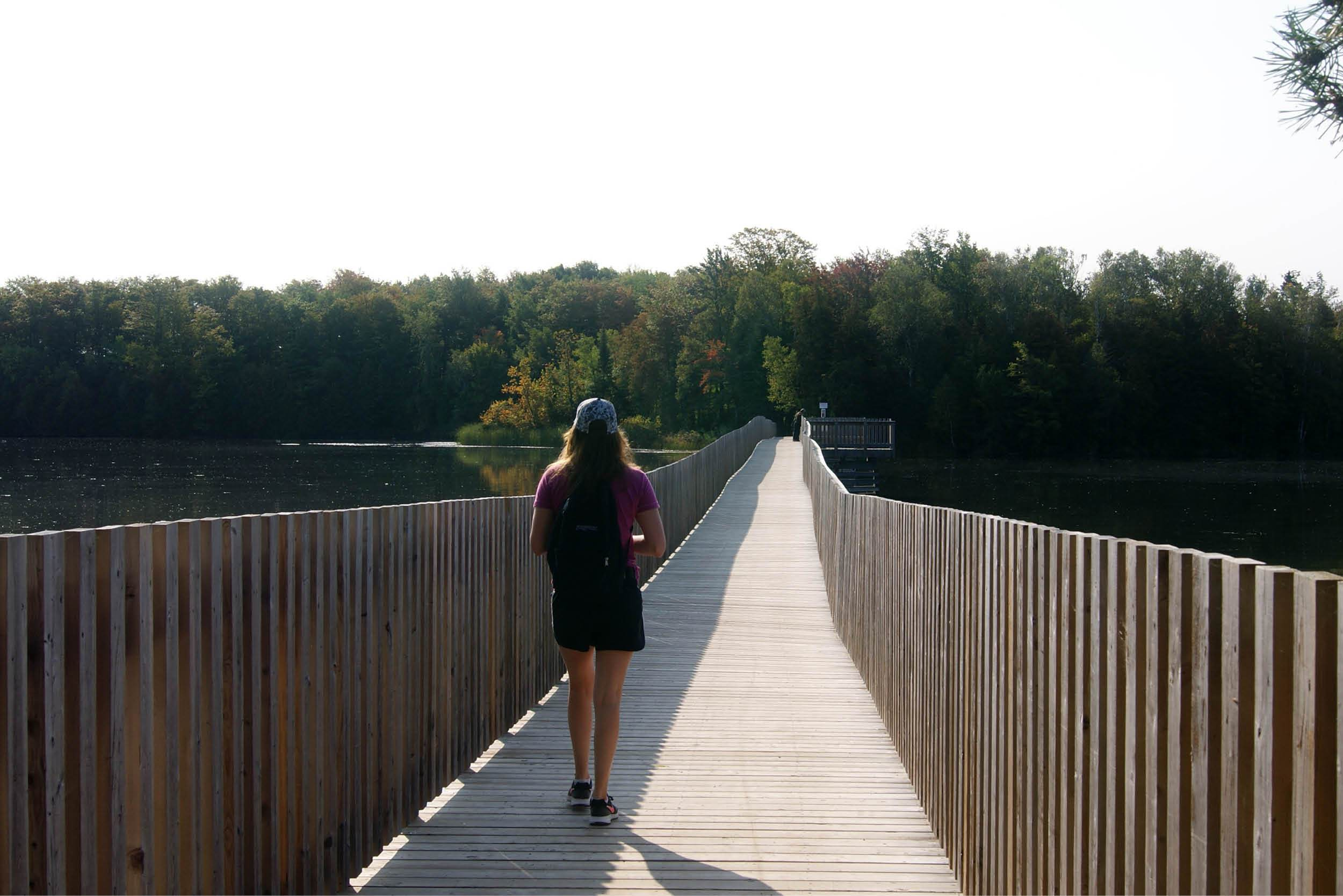 Woman hiking on boardwalk over lake
