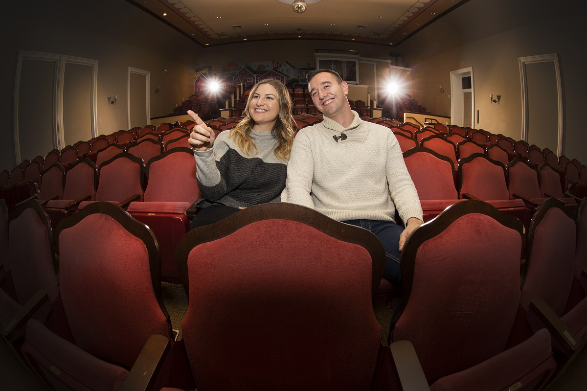 Couple sitting in red theatre seats